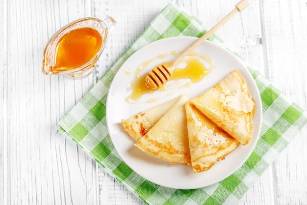 Süße pfannkuchen mit honig auf einer platte.