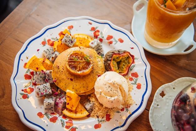Süße pfannkuchen mit honig und vanilleeis frucht mit orange fokus auf pfannkuchen