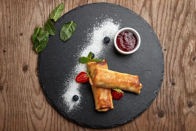 Süße pfannkuchen mit quark mit marmelade auf schwarzem schiefer
