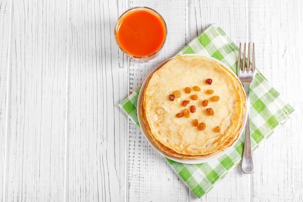 Süße pfannkuchen mit rosinen und saft.