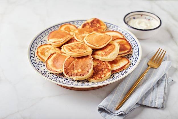 Süße pfannkuchen mit sauerrahm auf einem teller auf einem weißen tisch