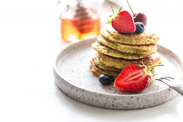 Süße pfannkuchen mit spinat, in honig getränkt, mit frischen erdbeeren