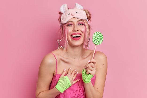 Süße positive kaukasische frau fühlt sich dankbar für kompliment hält süßigkeiten lächelt breit trägt weiche schlafmaske und kleid