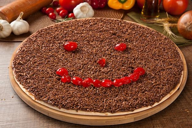 Süße rohe pizza mit schokolade und kirsche auf hölzernem raum