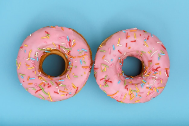 Süße rosa donuts auf einem blauen hintergrund, in form von augen ausgelegt, draufsicht