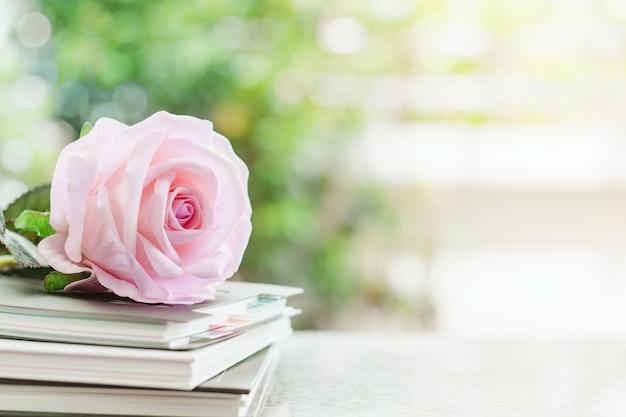 Süße rosarosenblume auf gewundenen notizbüchern gegen unscharfen natürlichen grünen hintergrund