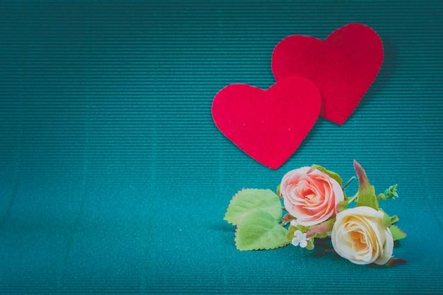 Süße rosen und 2 rote herzen auf grünem hintergrund, valentinstagkonzept.