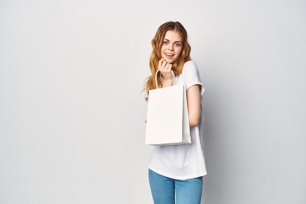 Süße rothaarige frau im weißen t-shirt packt shopping-lifestyle