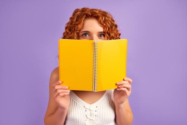 Süße rothaarige lockige mädchen student teenager spähen hinter einem notebook isoliert auf lila wand.