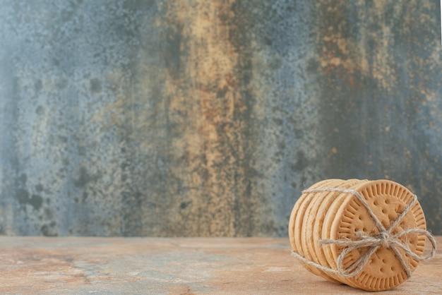 Süße runde kekse im seil auf marmorhintergrund