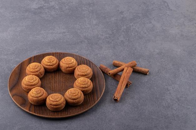 Süße runde kekse in teller auf steintisch gelegt.