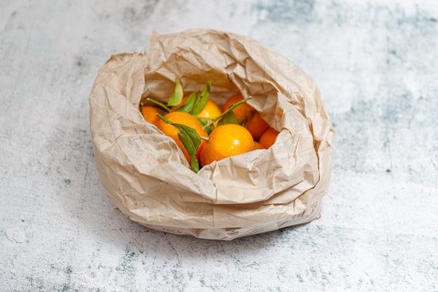 Süße saftige mandarinen in einer beigen papiertüte auf einem steinhintergrund