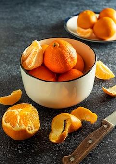 Süße saftige mandarinen in einer weißen schüssel, teilweise abgezogen, mit einem messer, auf dunklem hintergrund. ein symbol der winterferienzeit zu hause.