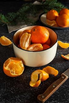 Süße saftige mandarinen in einer weißen schüssel, teilweise abgezogen, mit einem messer und einem tannenzweig auf dunklem hintergrund. ein symbol der winterferienzeit zu hause.
