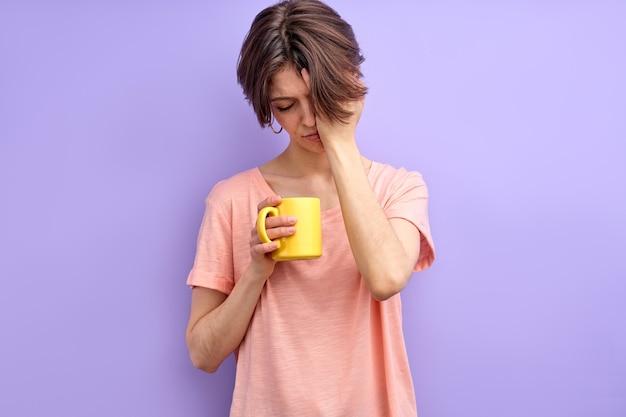 Süße schläfrige frau, die nicht genug schlaf hat, die morgens eine gelbe tasse in den händen hält.