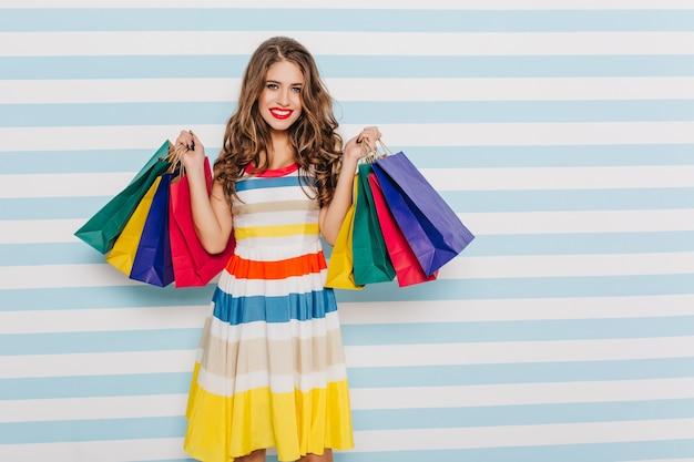 Süße, schöne brünette mit leuchtend rotem lippenstift im bunten kleid, das mit bunten einkaufstaschen auf gestreifter wand aufwirft