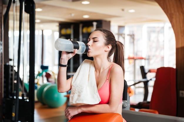 Süße schöne junge sportlerin trinkwasser beim training im fitnessstudio