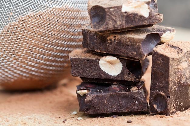 Süße schokolade mit in stücke gebrochenen nüssen, schokoladenstücke mit haselnüssen mit kakao und zucker, in teile geteilt tafelschokolade mit ganzen nüssen