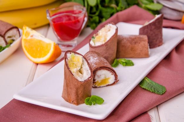 Süße schokoladenröllchen von pfannkuchen mit frischkäse, frischem obst und beerensauce auf weißem holz