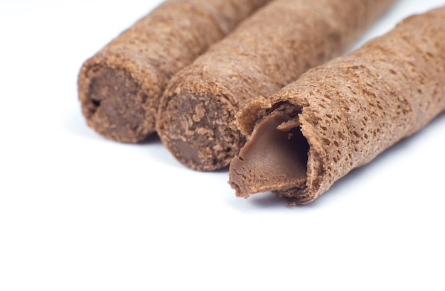 Süße schokoladenwaffelrollen kleben hautnah auf weißem hintergrund.