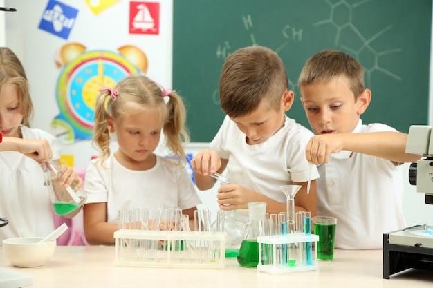 Süße schüler, die im chemieunterricht biochemische forschung betreiben