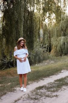 Süße schwangere umarmt ihren bauch. im park spazieren gehen. mädchen in einem weißen sommerkleid