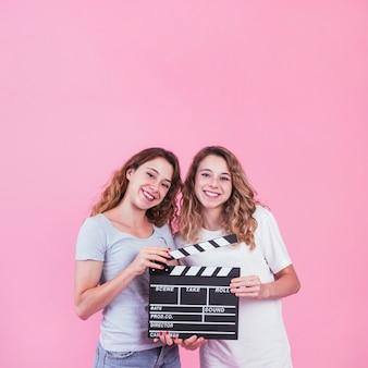 Süße schwester zwei, die klöppel in den händen gegen rosa hintergrund hält