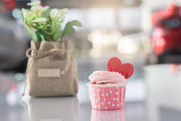 Süße selbst gemachte pastellfarbe des rosa kuchens auf bokeh verwischte hintergrund