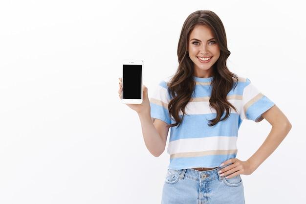 Süße, selbstbewusste, gut aussehende brünette mit lockigem haarschnitt zeigt smartphone-bildschirm, führt neue coole moderne app, online-shop, banksystem ein, lächelt erfreut, genehmigt eine tolle anwendung