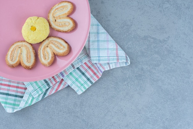 Süße snacks. hausgemachte kekse auf rosa teller.