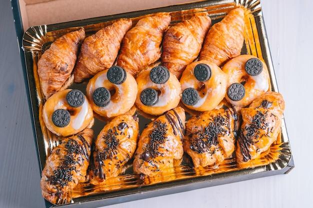 Süße snacks mit croissants und schokoladendonuts liefern in einer box-draufsicht