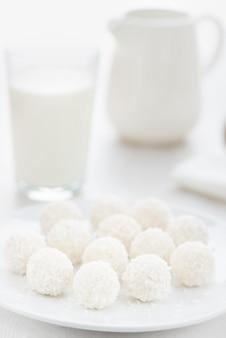 Süße süßigkeiten in kokosnusschips auf einem teller neben milch