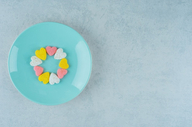 Süße süßigkeiten valentinstag herzen in einer blauen platte auf weißer oberfläche