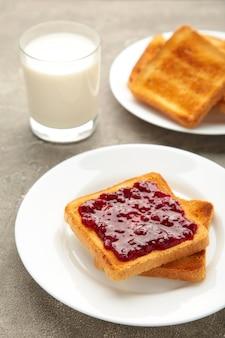 Süße toasts mit marmelade und obst mit milch zum frühstück, vertikal. ansicht von oben
