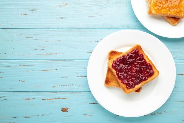 Süße toasts mit marmelade zum frühstück auf blau. ansicht von oben