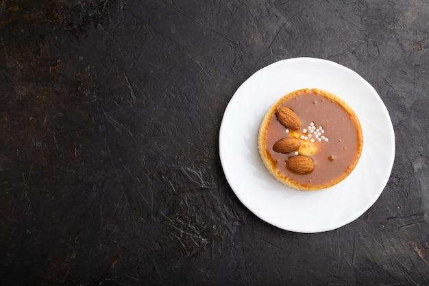 Süße törtchen mit mandeln und karamellcreme auf einem schwarzen betonhintergrund. draufsicht, flache lage, kopierraum.