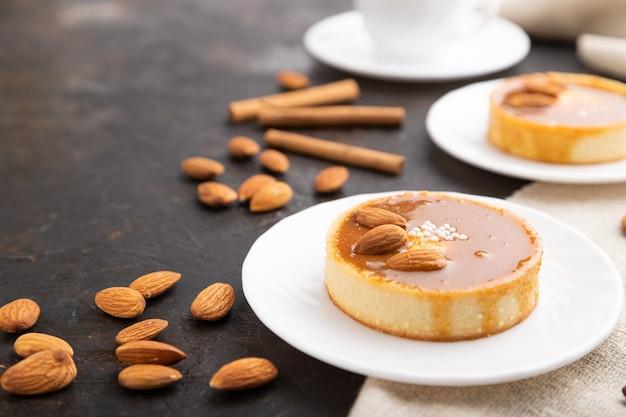 Süße törtchen mit mandeln und karamellcreme mit tasse kaffee auf schwarzem betonhintergrund und leinentextil. seitenansicht, nahaufnahme, selektiver fokus.