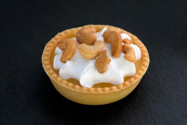 Süße törtchen mit nüssen cashewnüssen und schlagsahne auf einem schwarzen hintergrund