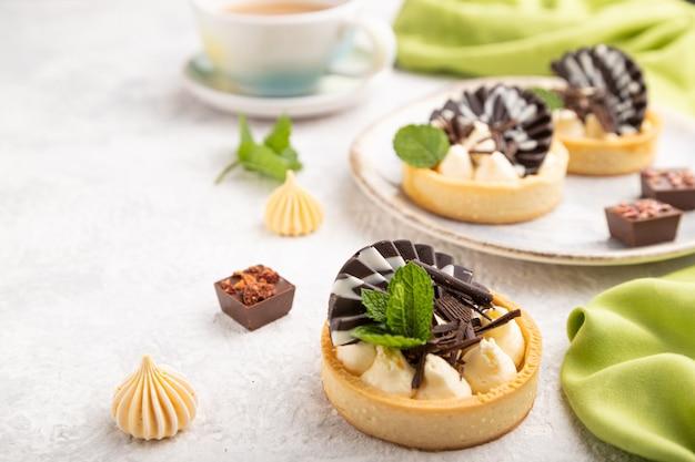 Süße törtchen mit schokoladen- und käsecreme mit tasse kaffee auf grauem betonhintergrund und grünem textil. seitenansicht, nahaufnahme, selektiver fokus.