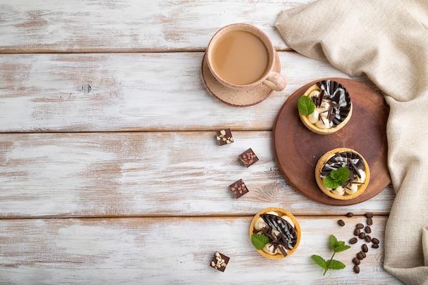 Süße törtchen mit schokoladen- und käsecreme mit tasse kaffee auf weißem hölzernem hintergrund und leinentextil. draufsicht, flache lage, kopierraum.