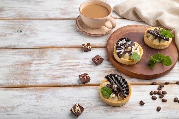 Süße törtchen mit schokoladen- und käsecreme mit tasse kaffee auf weißem hölzernem hintergrund und leinentextil. seitenansicht, kopierraum.