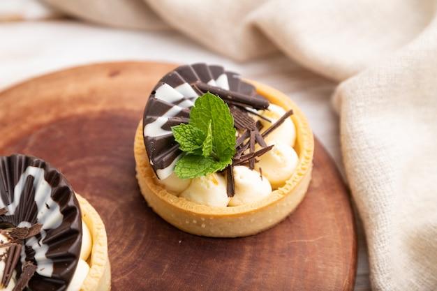 Süße törtchen mit schokoladen- und käsecreme mit tasse kaffee auf weißem hölzernem hintergrund und leinentextil. seitenansicht, nahaufnahme, selektiver fokus.