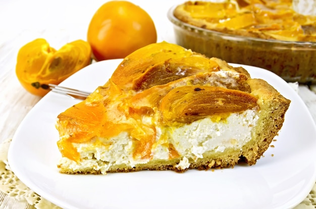 Süße torte mit quark und kaki, eine gabel in der weißen platte auf einer durchbrochenen silikonserviette, glaspfanne mit torte auf den hellen holzbrettern des hintergrundes
