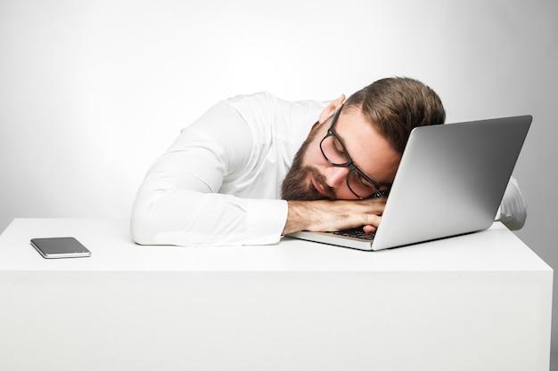 Süße träume am arbeitsplatz. das porträt eines müden, müden freiberuflers im weißen hemd sitzt im büro und schläft an seinem arbeitsplatz in der nähe des laptops. indoor, studioaufnahme, grauer hintergrund, isoliert