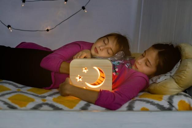 Süße träume, gute nacht und nachtlampen promo-konzept. nahaufnahme von zwei schönen 10-jährigen mädchenschwestern, die zusammen im gemütlichen bett mit hölzerner nachtlampe liegen und schlafen oder nickerchen machen.