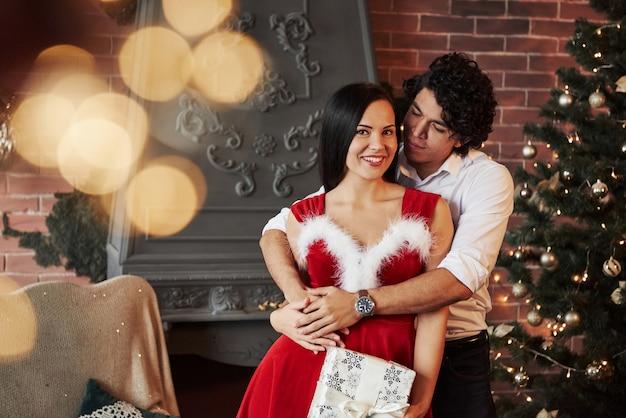 Süße umarmungen. schöne paare, die neues jahr im verzierten raum mit weihnachtsbaum und kamin hinten feiern