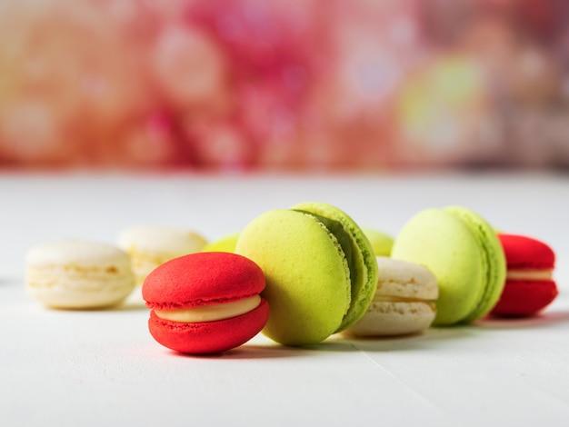Süße und bunte französische makronen auf buntem frühlingshintergrund mit kopienraum.