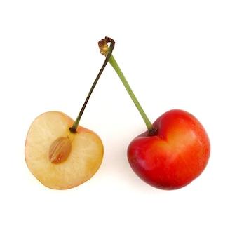 Süße und gesunde rainier-kirschen, geschnitten zur hälfte mit dem knochen, auf weißem hintergrund, frische früchte