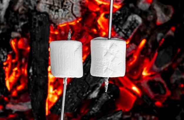 Süße und heiße marshmallows am stock über dem lagerfeuer