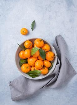 Süße und saftige mandarinen in einer grauen schüssel auf einem blauen hintergrund. draufsicht und kopierraum